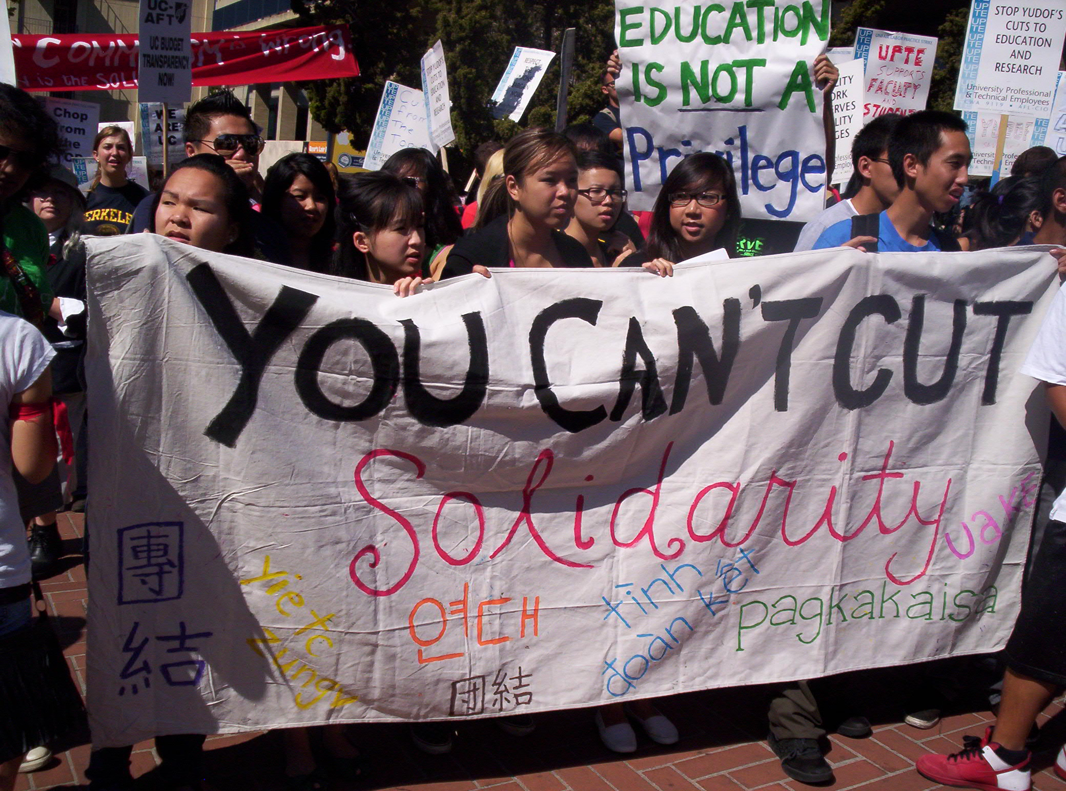 photo of students holding a banner that reads, you can't cut solidarity
