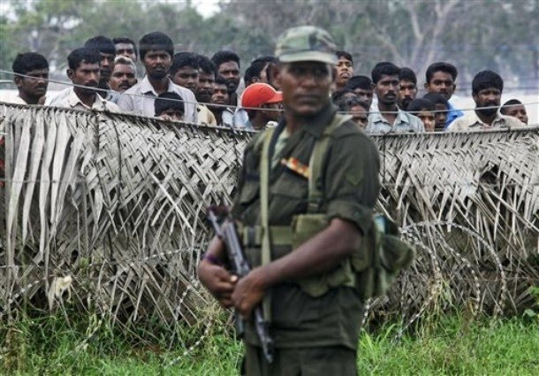 a_sri_lankan_army_soldier_stands_guard_next_to_a_fence.jpg