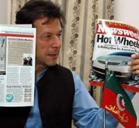 Pakistani cricket legend turned politician Imran Khan shows copies of the magazine during a news con
